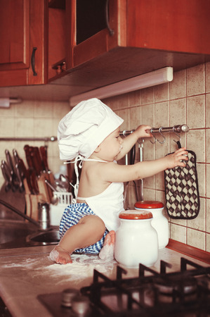 little dough: Little boy cook play dough on the table in an apron and chefs hat. The idea for your advertising