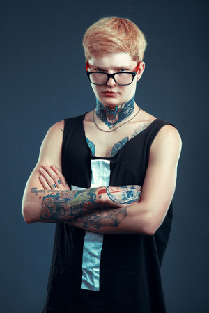 seriousness: A young blond man in glasses with a pierced nose and a tattoo is back. The concept of thoughtfulness, seriousness, confidence Stock Photo