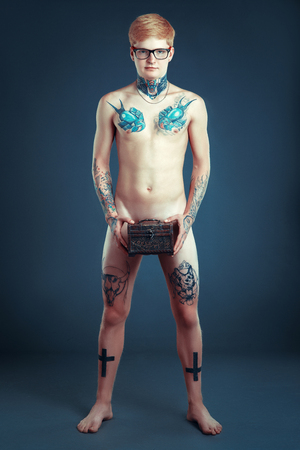 Young guy with glasses with a nose piercing is without clothes and holding a box in his hands, a body covered with tattoos Stock Photo