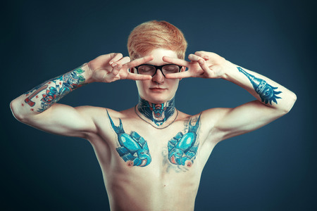 bare chested: Young guy in glasses with a pierced nose with a bare chested, body covered with tattoos Stock Photo