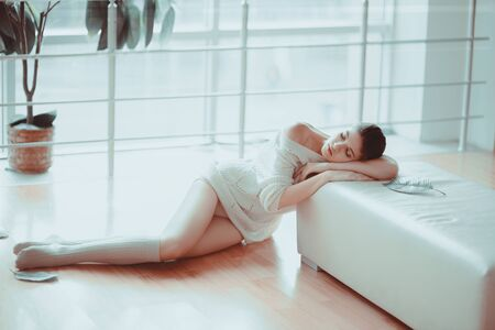 tenderness: Beautiful brunette girl model looks with a perfect figure sitting on the floor near his room. The concept is great, thoughtfulness and tenderness Stock Photo