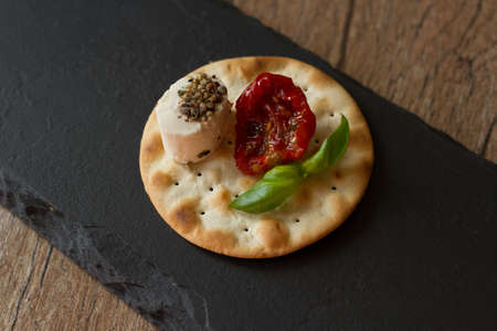 crackers with goat cheese, sun-dried tomatoes and basil photo