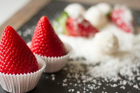 Raffaello coconut and strawberry on a black background
