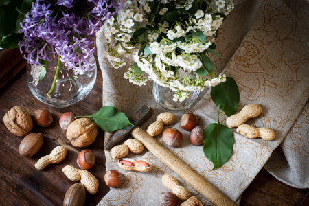 nuts with a hammer on the background of the fabric. with white flowers on a wooden table photo