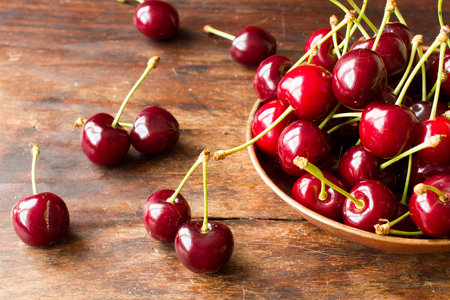 ripe cherries in a bowl made of copper on a wooden table photo