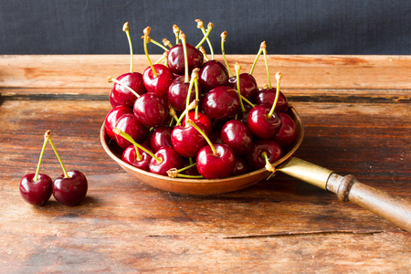 bronze bowl: ripe cherries in a bowl made of copper on a wooden table Stock Photo