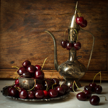 cherry hardwood: sweet cherry with a metal pitcher and dish in oriental style on a background of wood