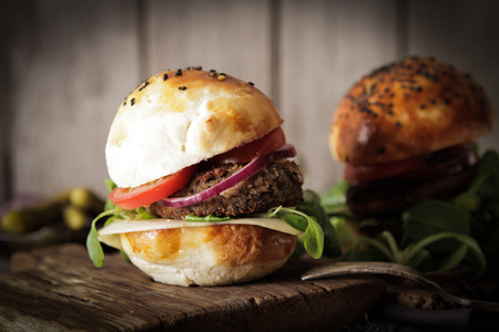 gourmet burger: homemade veggie burger in a bun with sesame seeds of beer. delicious fast food for vegans. on a wooden background