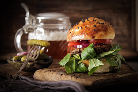 homemade veggie burger in a bun with sesame seeds of beer. delicious fast food for vegans. on a wooden background
