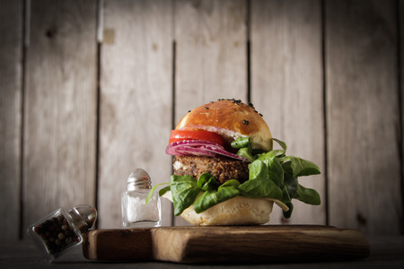delicious food: homemade veggie burger in a bun with sesame seeds of beer. delicious fast food for vegans. on a wooden background