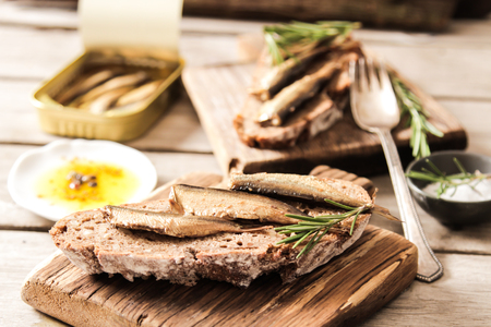gold cans: Sandwich Tapas with sardines, sprats with olives and salt on a wooden background Stock Photo