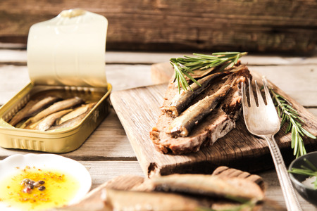 Sandwich Tapas with sardines, sprats with olives and salt on a wooden background Stock Photo