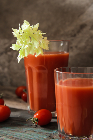 bloody: Bloody Mary with tomatoes and celery on a dark wooden background