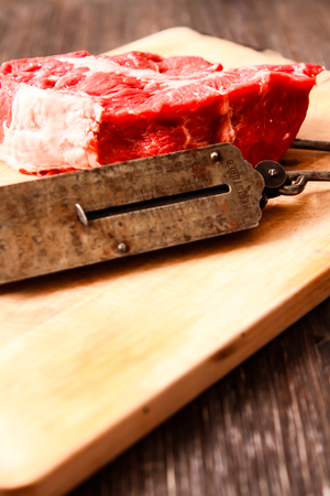hand weights: piece of raw meat with hand weights on the old wooden background