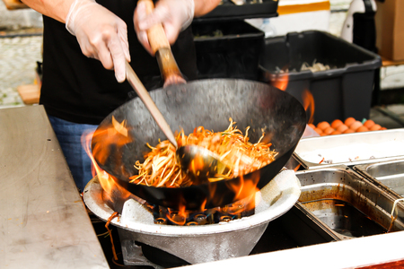 street food. fried noodles in a wok with chicken and shrimp on the open fire