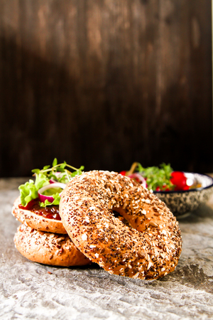 vegan bagel made at home with lettuce and sauce on a stone background Standard-Bild