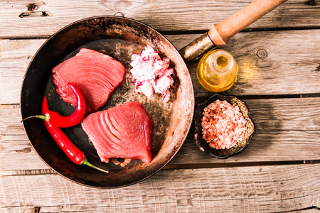 tuna steak in a frying pan with chili pepper on wooden background