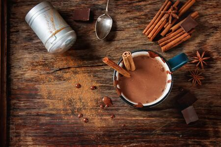 Homemade Peppermint hot chocolate with cinnamon sticks on a dark background. The area of the image with selective focus.