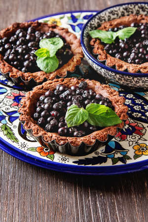 blueberry pie: Homemade chocolate blueberry pie with mint leaves on a wooden table