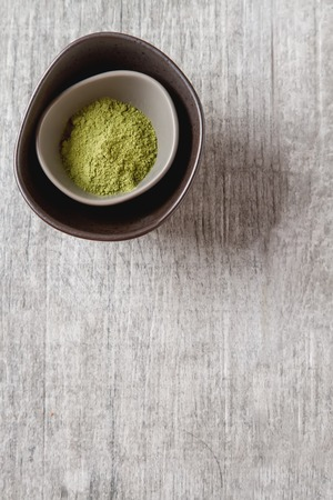 small plate: Dry Matcha tea in a small plate. Grey wood background Stock Photo