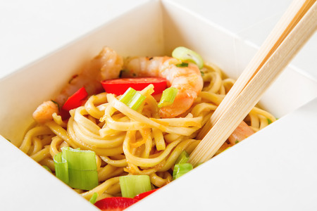 Noodles with vegetables, shrimp, green onions in sweet and sour Sauce with chopstikks on a gray stone background in white box. Selective focus.