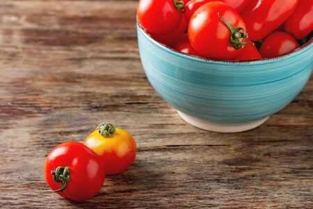 uncooked: Ripe red cherry tomatoes on blue plate. Dark wood background. Stock Photo