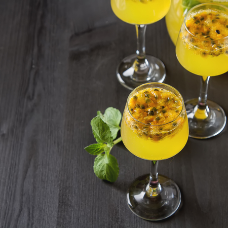 coctel de frutas: Alcoholic cocktail with fresh passion fruit with mint ice. Dark wood background. Foto de archivo