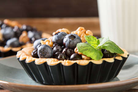 Homemade blueberry tart, walnut and mint with milk on a wooden table Stock Photo
