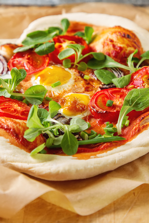 quail: Home Italian pizza with tomato and quail eggs salad on a baking paper.