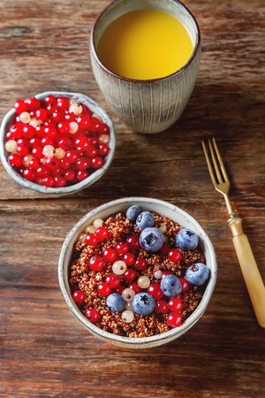 A healthy breakfast. Quinoa with berries in the old plate. Fresh orange juice. wood background