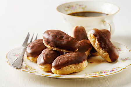 profiterole: French Chocolate cake, eclairs with a cup of hot black coffee in a vintage crockery, dessert fork. White wooden background