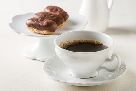 dessert fork: French Chocolate cake, eclairs with a cup of hot black coffee in a vintage crockery, dessert fork. White wooden background