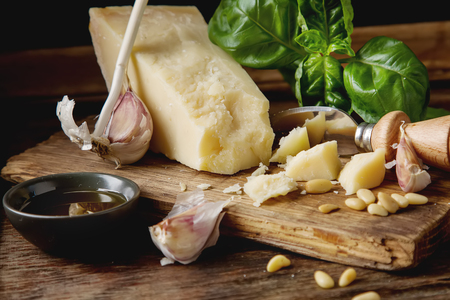 Italian parmesan cheese with knife fresh green basil,  oil, pine nuts and garlic. Ingredients for the pesto. Dark wood background Stock Photo