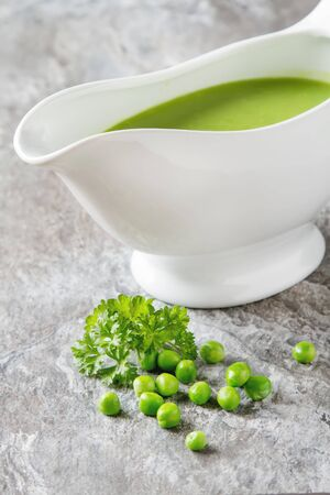 tureen: Pea soup puree in a white tureen. Stone slate background.