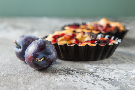Homemade cake tartlets with plum  old stone background Stock Photo