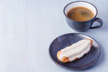 Traditional French cuisine. Eclair drizzled with white icing on a blue plate with  cup of hot black coffee. Light wood background