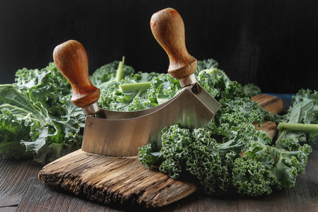 Fresh chopped Kale Italian salad on old wooden board with a knife. Dark background