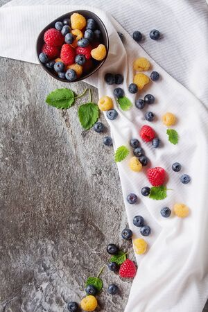 Ripe berries. White, red raspberries and blueberries in brown cup of white cloth. Grey stone background Stock Photo