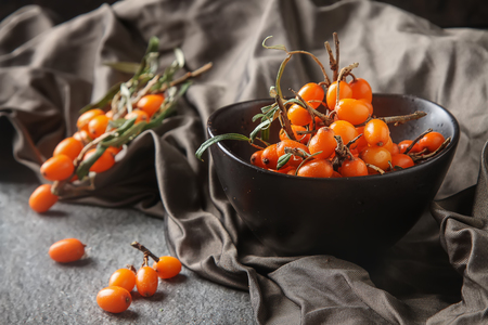 Fresh sea buckthorn on a branch lying on plate, juice. Gray background