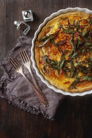 Traditional French cake. quiche with chard in white. Dark wood background. free space text. Top view