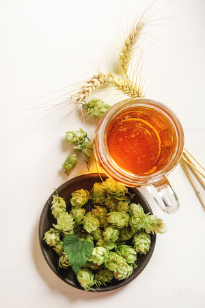 A glass of beer, production ingredients. Fresh-picked whole hops and wheat close-up. White wooden background. Stock Photo