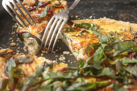 Traditional French cake. quiche with chard. Dark background. free space text. Top view