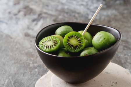 New Zealand exotic food. Berry nergi, or small kiwi. In a brown plate. Grey stone background
