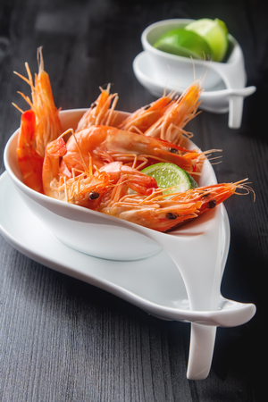 Fresh raw shrimps in a bowl on a wooden table. Eating seafood. Dark background Standard-Bild