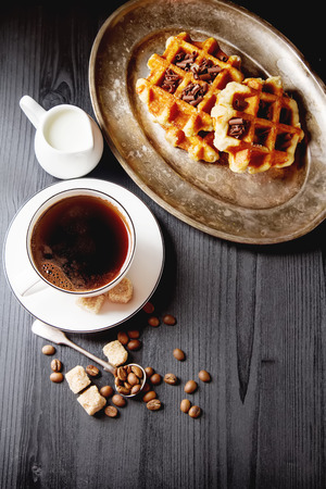 Homemade belgian waffles, white ceramic cup of coffee, milk, teaspoon and coffee beans. Dark rustic background. Space for text in the center