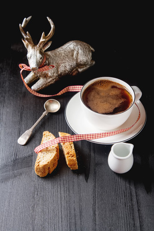 Traditional Italian food. Cantuccini cookies with black coffee in a white mug, milk. Dark wood background Stock Photo