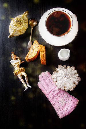 Traditional Italian food. Christmas toys. Cantuccini cookies with black coffee in a white mug, milk. Dark wood background