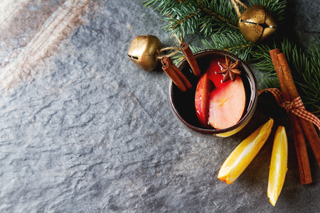 Mulled red wine with apples and oranges. Cinnamon, sugar, anise, Christmas tree branches. Gray background