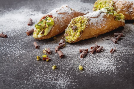 Sweet homemade cannoli stuffed with ricotta cheese cream and pistachial Sicilian dessert. Italian pastry.