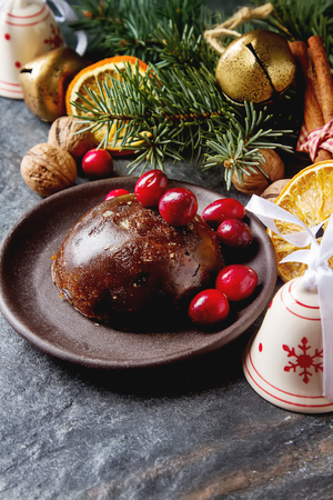 sultanas: Christmas chocolate pudding with cranberries, walnuts, cinnamon, apples and oranges. Dark background Stock Photo